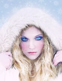 Snow Queen Fier Blue Eyes - Snowflakes. Model with affects added for interest i.e. fierce icy blue eyes, snowflakes blended into image. White fur hooded jacket royalty free stock photo