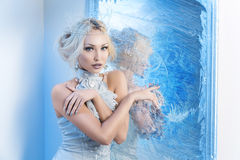 Snow queen near frozen mirror. Beautiful young woman in crown and silver top standing near frozen mirror. Snow queen. Copy space Royalty Free Stock Photos