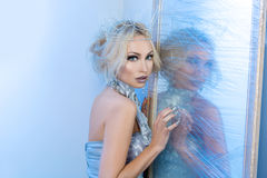 Snow queen near frozen mirror. Beautiful young woman in crown and silver top standing near frozen mirror. Snow queen. Copy space Royalty Free Stock Images