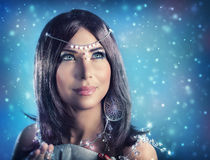Snow queen portrait. Portrait of pretty female wearing stylish crystal jewelery over dark snowy background, gorgeous snow queen looking up, fashion and beauty Stock Images