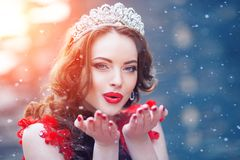 Snow Queen in red. Winter woman in crown in a red dress and red. Lipstick. Girl with snowflakes Stock Photos