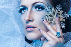 Snow Queen and Snowflake. Girl with scenic make-up of the Snow Queen is holding a snowflake shot closeup Royalty Free Stock Photography
