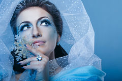 Snow Queen and Snowflake. Girl with scenic make-up of the Snow Queen is holding a snowflake shot closeup Royalty Free Stock Images