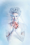 Snow queen with an unusual makeup and heart in hands Stock Photo