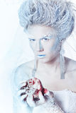 Snow queen with an unusual makeup and heart in hands Stock Images
