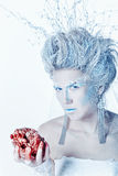 Snow queen with an unusual makeup and heart in hands. Mysterious and unusual girl with face art in the form of the Snow Queen. Girl holding a human heart in the Stock Photography