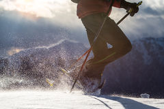 Snow raised by a man walking with snowshoes. Royalty Free Stock Photography
