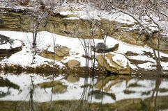 Snow reflected in a Pond. Snow patches on the bank of a still pond Stock Photography