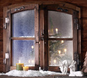 Snow Reindeer and Lighted Candles at Window Pane Stock Photography