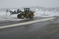 Snow removal. Front loader clearing snow on exit of interstate highway 70 in Colorado Stock Photo