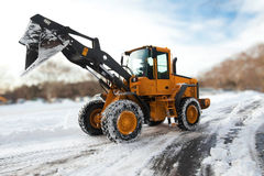 Snow removal. Yellow tractor removing snow from a blizzard Stock Photo