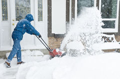 Snow Removal. Man clearing the front of the house with a snow blower during a winter storm Stock Photography