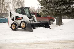 Snow removal. Bobcat removing snow in a parking lot Stock Photo