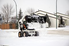 Snow removal. Bobcat removing snow from the road Royalty Free Stock Images