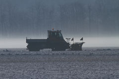 Snow plow at work in morning ground fog Stock Images