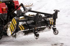 Snow removal equipment in work. Cleaning the streets of snow with a tractor royalty free stock photography