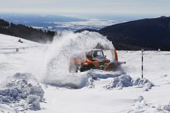Snow removal machine blower on mountain road. Snow removal machine blows the snow on a mountain road. The road is not visible because of the thick snow royalty free stock photography