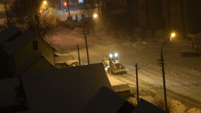 Snow removal machine cleaning road at night stock footage