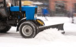 Snow removal machine cleaning the street from snow. Snowplow truck removing snow on the street after blizzard. Intentional motion blur stock photo