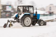 Snow removal machine cleaning the street from snow. Snowplow truck removing snow on the street after blizzard. Intentional motion blur stock images