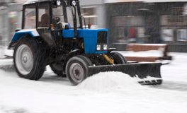 Snow removal machine cleaning the street from snow. Snowplow truck removing snow on the street after blizzard. Intentional motion blur royalty free stock photo