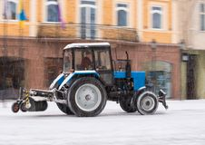Snow removal machine cleaning the street from snow. Snowplow truck removing snow on the street after blizzard. Intentional motion blur stock image