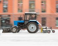 Snow removal machine cleaning the street from snow. Snowplow truck removing snow on the street after blizzard. Intentional motion blur royalty free stock photography