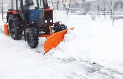 Snow removal machine cleans the street of snow. Cleaning road from snow. Storm at winter stock photo