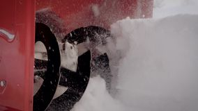 Closeup of the rotating blade of a snowplow removes snow drifts after a snowfall. Snow removal machine clears snow after a snowfall on a winter day. Close up of stock footage
