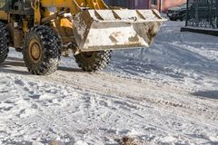 Snow removal snow machine on the road in  spring. Snow removal snow machine on the road in winter or spring royalty free stock photo