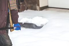 Snow removal. man cleans snow from yard plastic shovel Royalty Free Stock Images