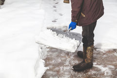 Snow removal. man cleans snow from yard plastic shovel Stock Photos
