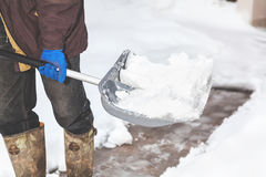 Snow removal. man cleans snow from yard plastic shovel Stock Images
