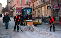 Snow removal on streets of old town. Uzhgorod, Ukraine - January 19, 2017: snow removal on streets of old town. people remove snow huge amount of snow with the Royalty Free Stock Photography