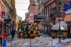 Snow removal on streets of old town. Uzhgorod, Ukraine - January 19, 2017: snow removal on streets of old town. people remove snow huge amount of snow with the Stock Image