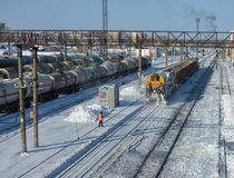 Snow removal train clears railway at the station. Lot of cargo cars and oil tanks at the back. Sunny winter day somewhere in Siberia Royalty Free Stock Image
