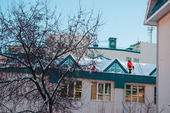 Snow removal in winter with the roof Stock Photos