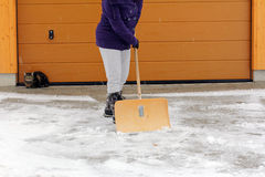 Snow removal in winter. A woman admits snow in front of a garage Stock Photography