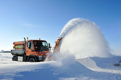 Snow removal working. Snow blower  removing snow for cleaning road Royalty Free Stock Images