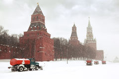 Snow-remover trucks on road near Kremlin. Four snow-remover trucks on the road near Kremlin chiming clock of the Spasskaya Tower in Moscow, Russia at wintertime Stock Images