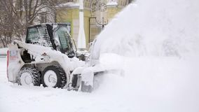 Snow-removing car. Snow removal after a snowfall in the city Park.  stock video footage