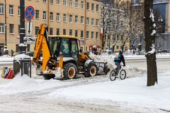 The snow-removing machine clears the snow from the road. One bicyclist is riding on a snow-covered road stock photos