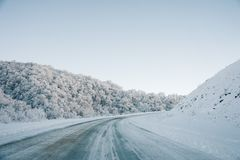 Snow road and car tracks on the road in the winter in the North Caucasus. Snow-covered trees and mountains. The concept. Of winter travel by car Royalty Free Stock Photography