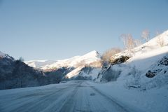 Snow road and car tracks on the road in the winter in the North Caucasus. Snow-covered trees and mountains. The concept. Of winter travel by car Stock Image