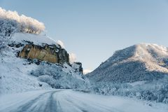 Snow road and car tracks on the road in the winter in the North Caucasus. Snow-covered trees and mountains. The concept. Of winter travel by car Stock Photography