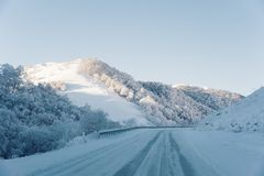Snow road and car tracks on the road in the winter in the North Caucasus. Snow-covered trees and mountains. The concept. Of winter travel by car royalty free stock image