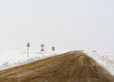 Snow road. Crossroad in a stormy winter day with road signs Royalty Free Stock Photography