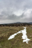 Snow road to the foggy mountain with dramatic grey sky. Russia, Stary Krym. Royalty Free Stock Photo