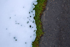 Snow in road with turf grass line Royalty Free Stock Image