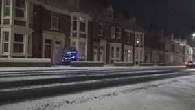 Snow on road in UK. Snow on road- beautiful view on a snow falling down on the road and residential buildings, United Kingdom, Newcastle upon Tyne stock video